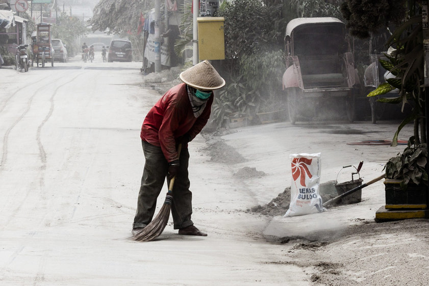 A figure sweeps ash in Yogyakarta during the 2014 eruption of Kelud